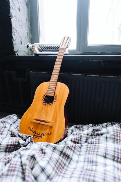 Houten akoestische gitaar op het bed dichtbij venster. Premium Foto