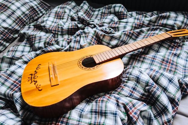 Houten akoestische gitaar op het bed. Premium Foto