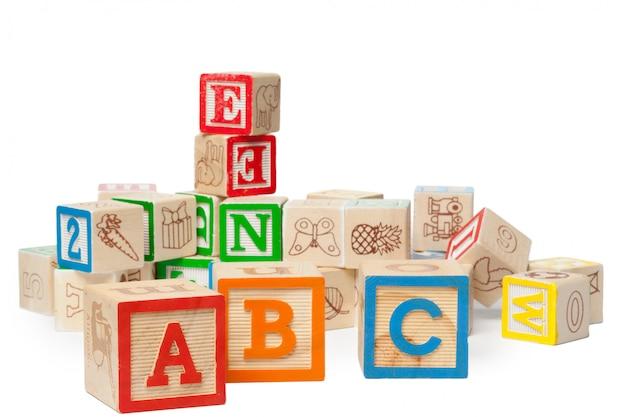 Houten alfabetblokken die op witte achtergrond worden geïsoleerd Premium Foto