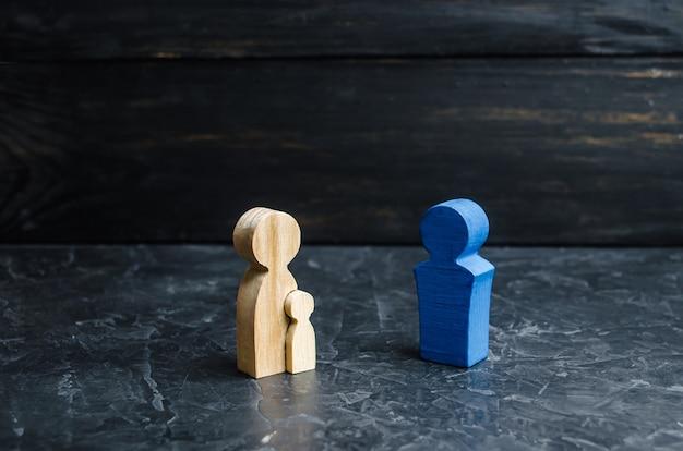 Houten beeldjes van moeder met kind en vader. het concept van een sterk gezin, patronage. Premium Foto