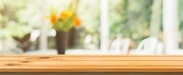Houten bord lege tafelblad wazige achtergrond. perspectief bruin houten tafel over vervagen in de koffie winkel achtergrond. panoramische banner - kan gebruikt worden voor montage producten display of ontwerp. Gratis Foto