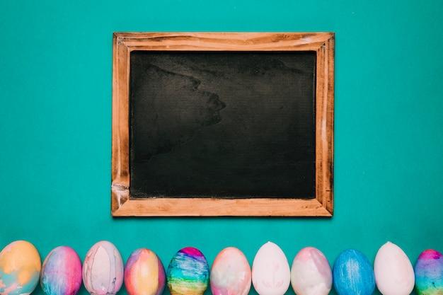 Houten bord over de rij met geschilderde paaseieren op groene achtergrond Gratis Foto