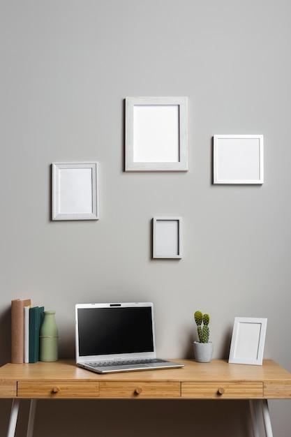 Houten bureau met laptop en fotolijsten Gratis Foto