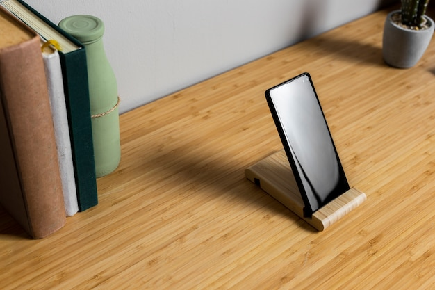 Houten bureau met zwarte smartphone en boeken Gratis Foto