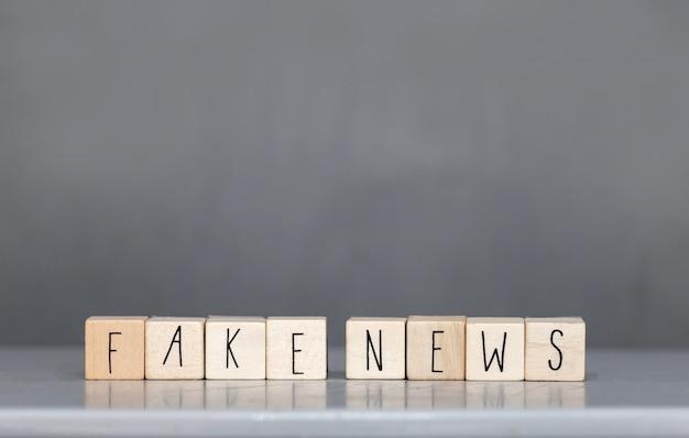 Houten cubess met de woorden fake news op grijze muur, fake news-concept sociale media Premium Foto