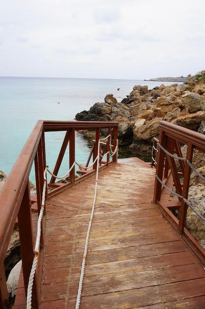 Houten dok in de buurt van de oceaan met een rotsachtige kust Gratis Foto