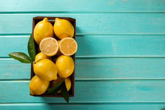 Houten doos met citroenen op groene houten achtergrond Premium Foto