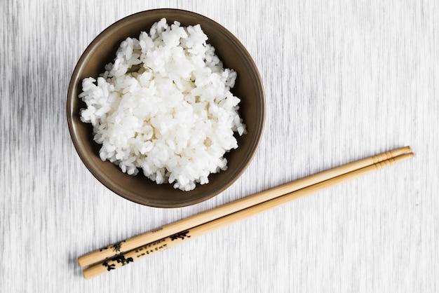 Houten eetstokjes in de buurt van kom met rijst Gratis Foto