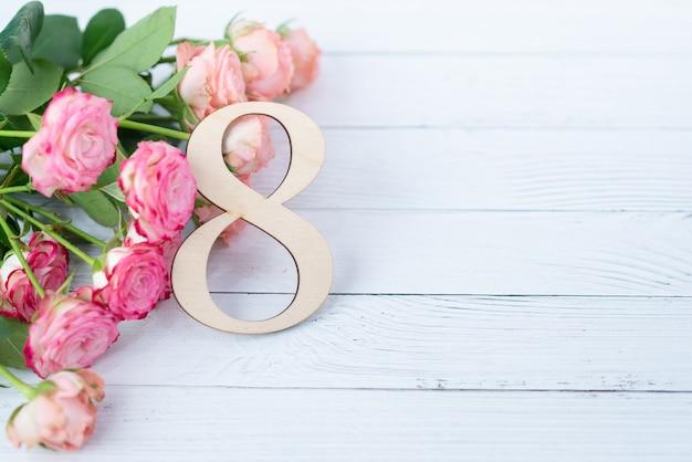 Houten figuur 8 met roze bloemen op een witte tafel. internationale vrouwendag. 8 maart Premium Foto