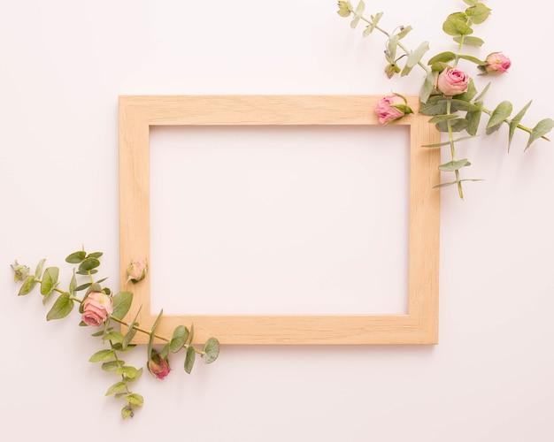 Houten fotolijstje versierd met roze rozen en eucalyptus Gratis Foto