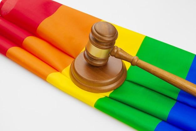 Houten geïsoleerde rechterhamer en lgbt regenboogvlag Premium Foto