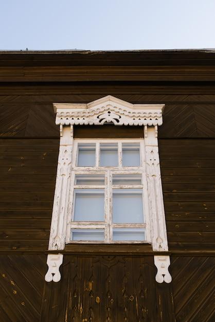 Houten gesneden raamkozijn in een houten russisch huis Premium Foto