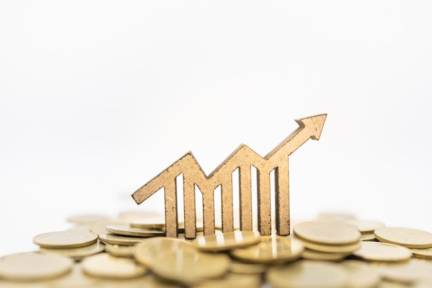 Houten grafiek groei met pijlpictogram op stapel van gouden munten. Premium Foto