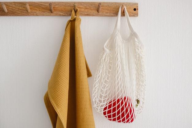 Houten haakhanger met witte eco tas met een paprika en een gele katoenen handdoek, hangend aan een witte muur in de moderne keuken Premium Foto
