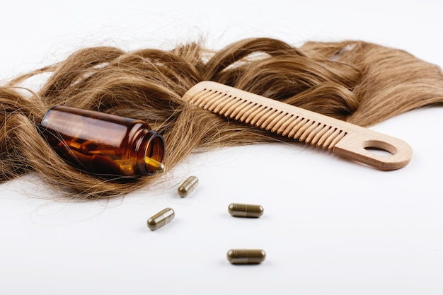 Houten haarkam en fles met vitamines liggen op krullen van bruin haar Gratis Foto