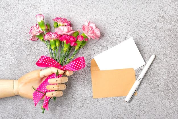 Houten hand houden kleurrijke boeket van verschillende roze anjer bloemen, ambachtelijke envelop, papier geïsoleerd op een grijze achtergrond Premium Foto