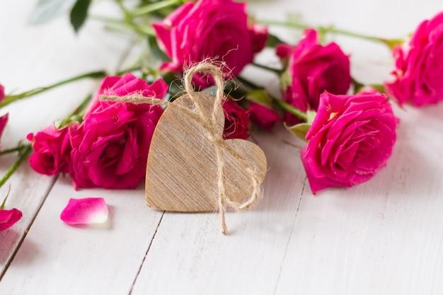 Houten hart en roze rozen op houten witte tafel voor valentijnsdag Premium Foto