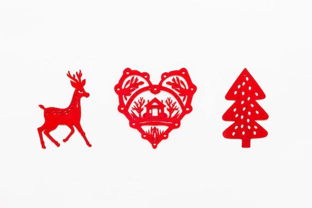 Houten hart met silhouet van huis, lopende herten, dennenboom. decoratieve rode kerstdecoratie. Premium Foto