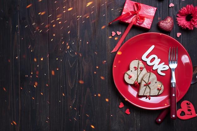 Houten hart op rode plaat voor valentijnsdag met liefde concept voor valentijnsdag Premium Foto