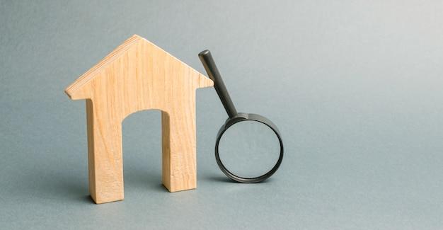 Houten huis en vergrootglas. Premium Foto