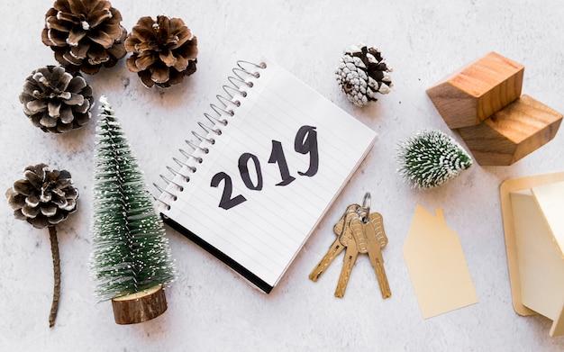 Houten huis model; kerstboom; dennenappels; sleutels en 2019 geschreven op spiraalvormige blocnote tegen concrete achtergrond Gratis Foto