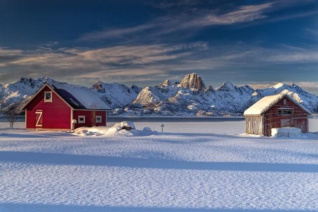 Houten huisjes op een met sneeuw bedekt veld omgeven door besneeuwde bergen in noorwegen Gratis Foto