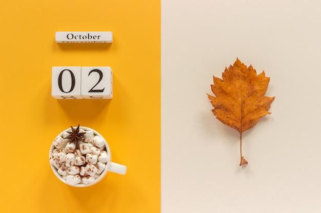 Houten kalender 2 oktober, kopje cacao met marshmallows en gele herfstbladeren op gele beige achtergrond. Premium Foto