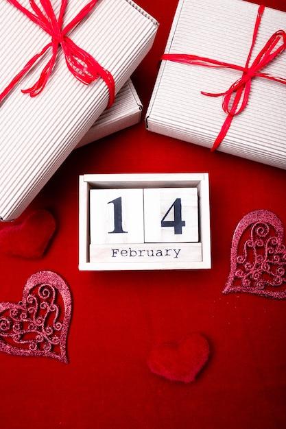 Houten kalender show van 14 februari met rood hart en geschenkdozen. Premium Foto