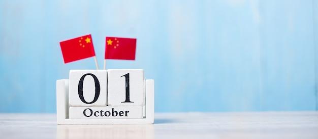Houten kalender van 1 oktober met miniatuur china vlaggetjes. Premium Foto
