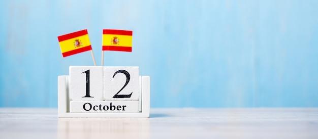 Houten kalender van 12 oktober met miniatuur vlaggen van spanje. Premium Foto