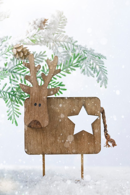 Houten kerst herten met fir tree op sneeuw. kerstmis of nieuwjaar concept Premium Foto