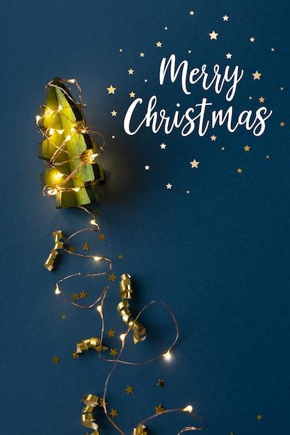 Houten kerstboom in de vorm van een raket op een donkerblauwe achtergrond. straal spoor van slinger. het concept van kerstmis. afbeelding van de raket Premium Foto