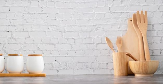 Houten keukengerei en koppen op de witte achtergrond van de bakstenen muurtextuur. Premium Foto