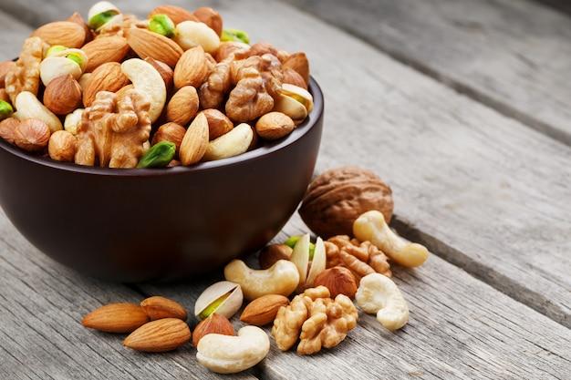 Houten kom met gemengde noten op houten grijs. walnoot, pistachenoten, amandelen, hazelnoten en cashewnoten, walnoot. Premium Foto