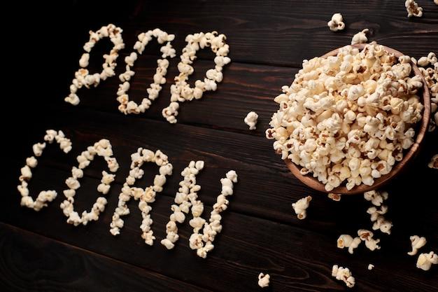 Houten kom met zoute popcorn op een houten tafel. donkere achtergrond selectieve aandacht. plat liggen. u автор: ugryumov igor Premium Foto