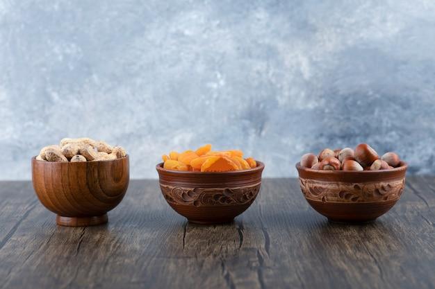 Houten kommen vol gezonde noten met gedroogde abrikozenvruchten op houten tafel. Gratis Foto