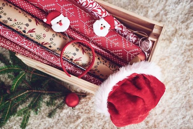 Houten krat met kerstpapier en kerstmuts Gratis Foto