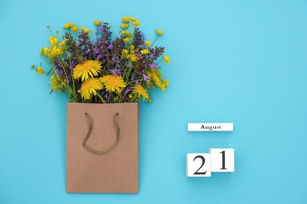 Houten kubussen kalender 21 augustus en veld kleurrijke rustieke bloemen in ambachtelijke pakket Premium Foto
