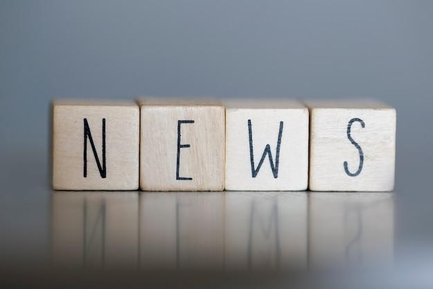 Houten kubussen met het woord nieuws, zaken of media concept op grijze muur Premium Foto