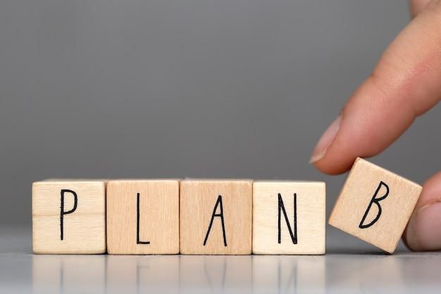 Houten kubussen met het woord plan b op grijze achtergrond en menselijke vinger, bedrijfsconceptenachtergrond Premium Foto