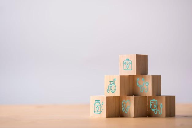 Houten kubussen stapelen van gezondheidszorg geneeskunde en ziekenhuis pictogram op tafel. zorgverzekeringen en investeringen. Premium Foto