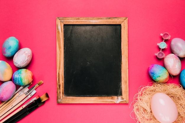 Houten leeg bord met paaseieren; verf penselen en verf kleur op roze achtergrond Gratis Foto