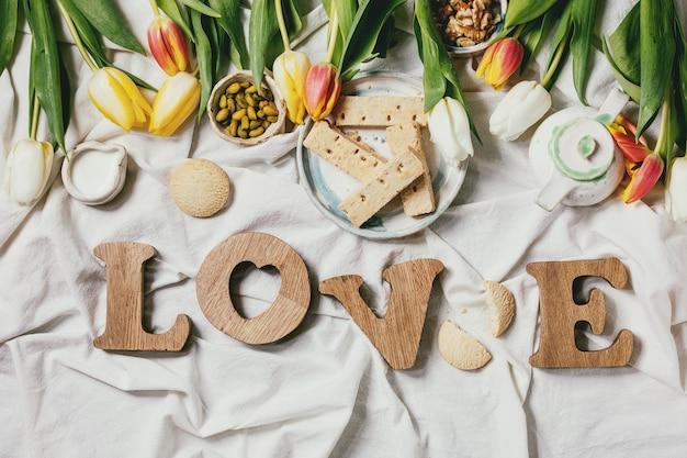 Houten letters love met snacks en tulpenbloemen Premium Foto