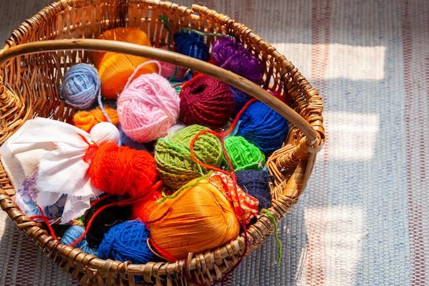 Houten mand met regenboog natuurlijke ballen van garen op een oud traditioneel tapijt. Premium Foto