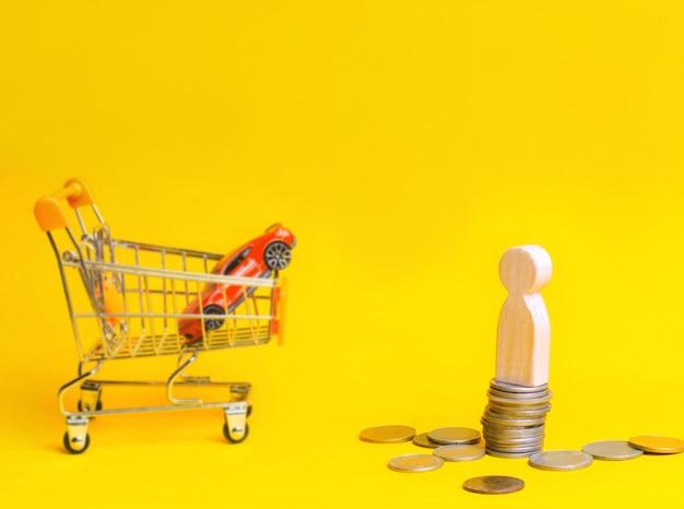 Houten manentribune op muntstukken op de achtergrond van een auto en een mand van een supermarkt. Premium Foto