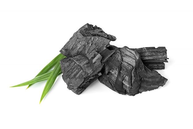 Houten natuurlijke houtskool met pandanblad dat op witte oppervlakte wordt geïsoleerd Premium Foto
