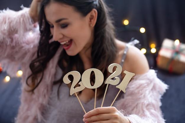 Houten nieuwjaarsnummer op de achtergrond van een blij gezicht meisje close-up. Gratis Foto