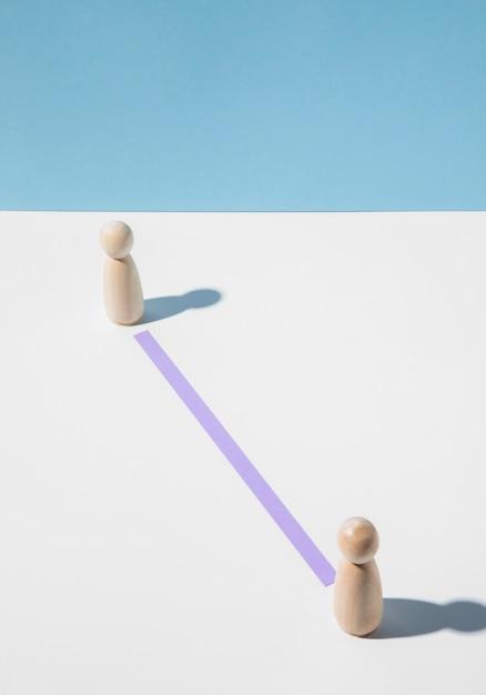 Houten pionnen met onderlinge afstand voor bescherming tegen het coronavirus Gratis Foto
