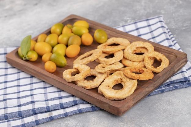 Houten plaat van verse cumquats en gedroogde appelringen op marmeren achtergrond. Gratis Foto