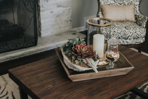 Houten pot op een houten tafel met bloemen en kaarsen op het in de buurt van een fauteuil en een open haard Gratis Foto